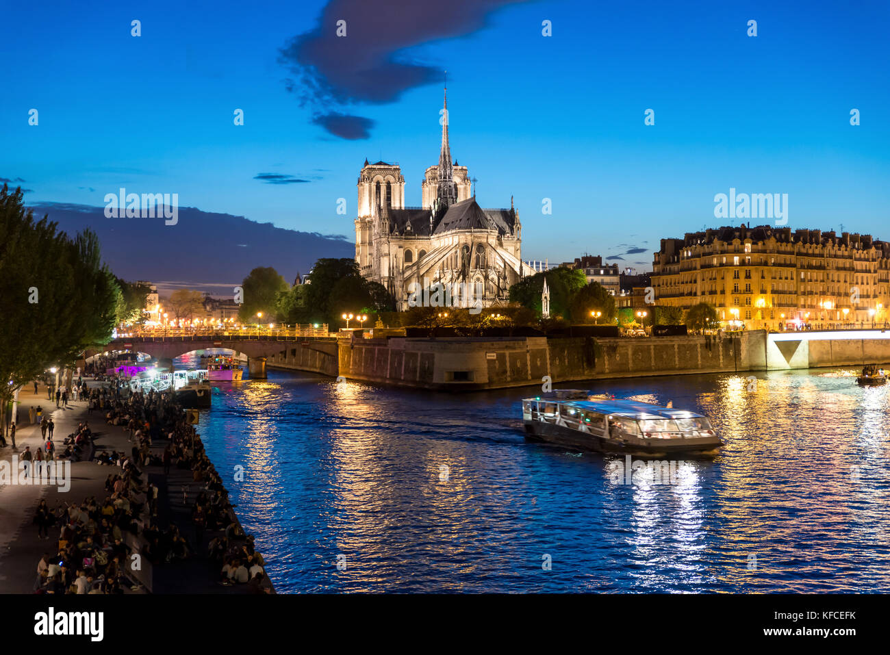 Notre Dame de Paris with cruise ship on Seine river at night in Paris, France Stock Photo