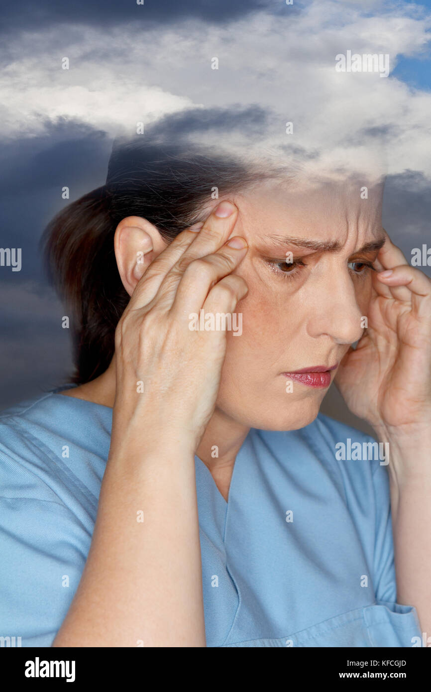 Middle aged woman suffering from an acute headache or migraine attack due to weather sensitivity Stock Photo