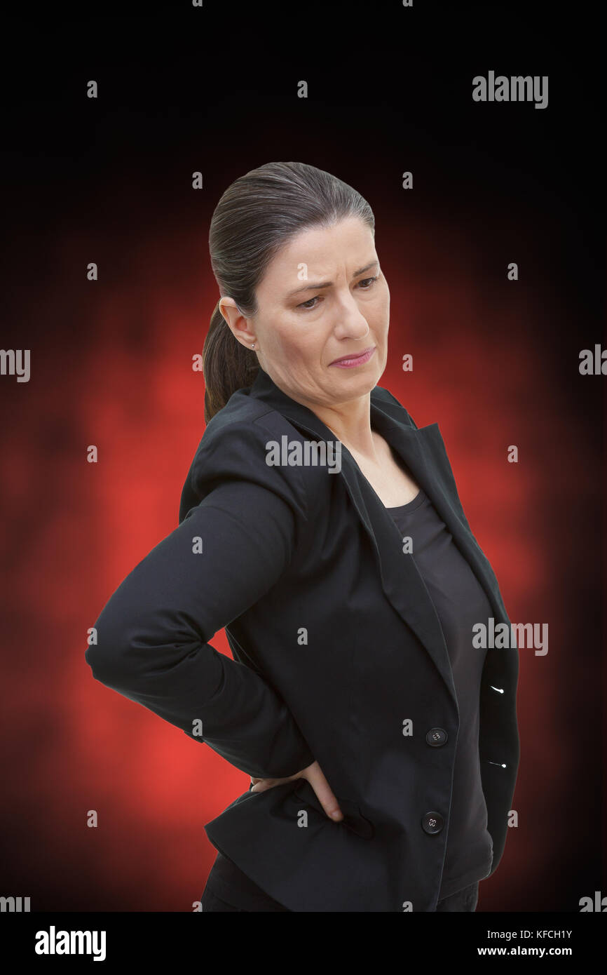 Middle aged woman with chronic pain syndrome fibromyalgia suffering from acute backache, on red and black background Stock Photo