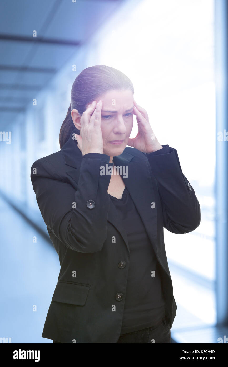 Middle aged woman with chronic pain syndrome fibromyalgia suffering from an acute migraine attack at her office Stock Photo