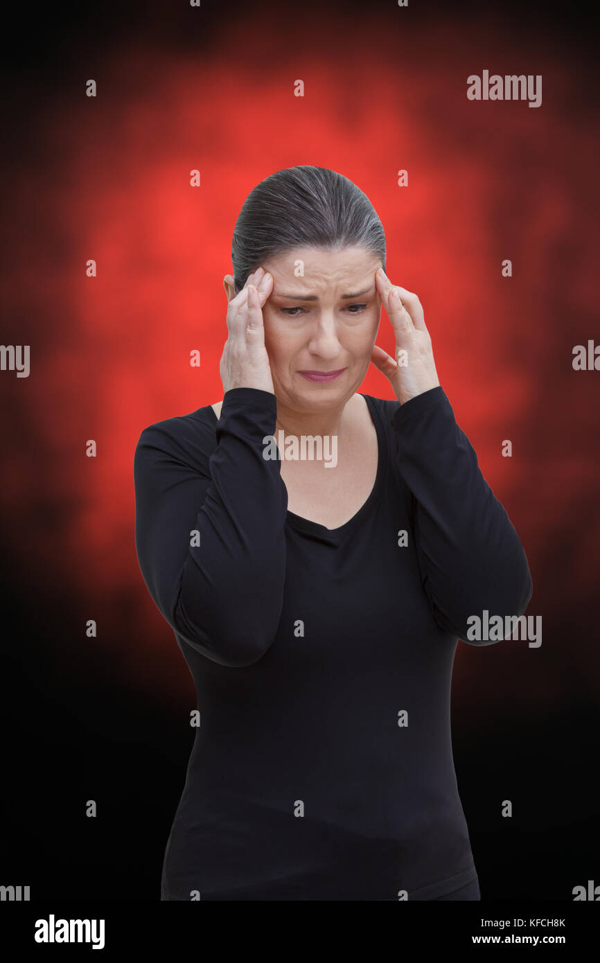 Middle aged woman with chronic pain syndrome fibromyalgia suffering from acute pain in the head, on red and black Stock Photo
