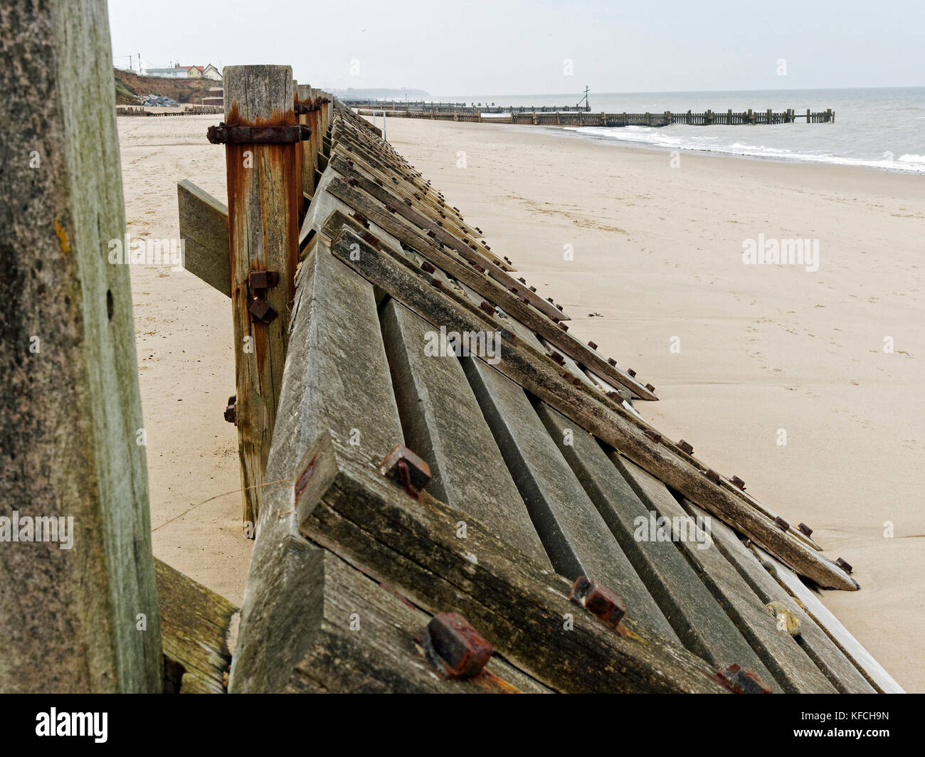 A sloped timber wall or groyne designed to break the strength of waves to provide protection for soft rock cliffs - Stock Image