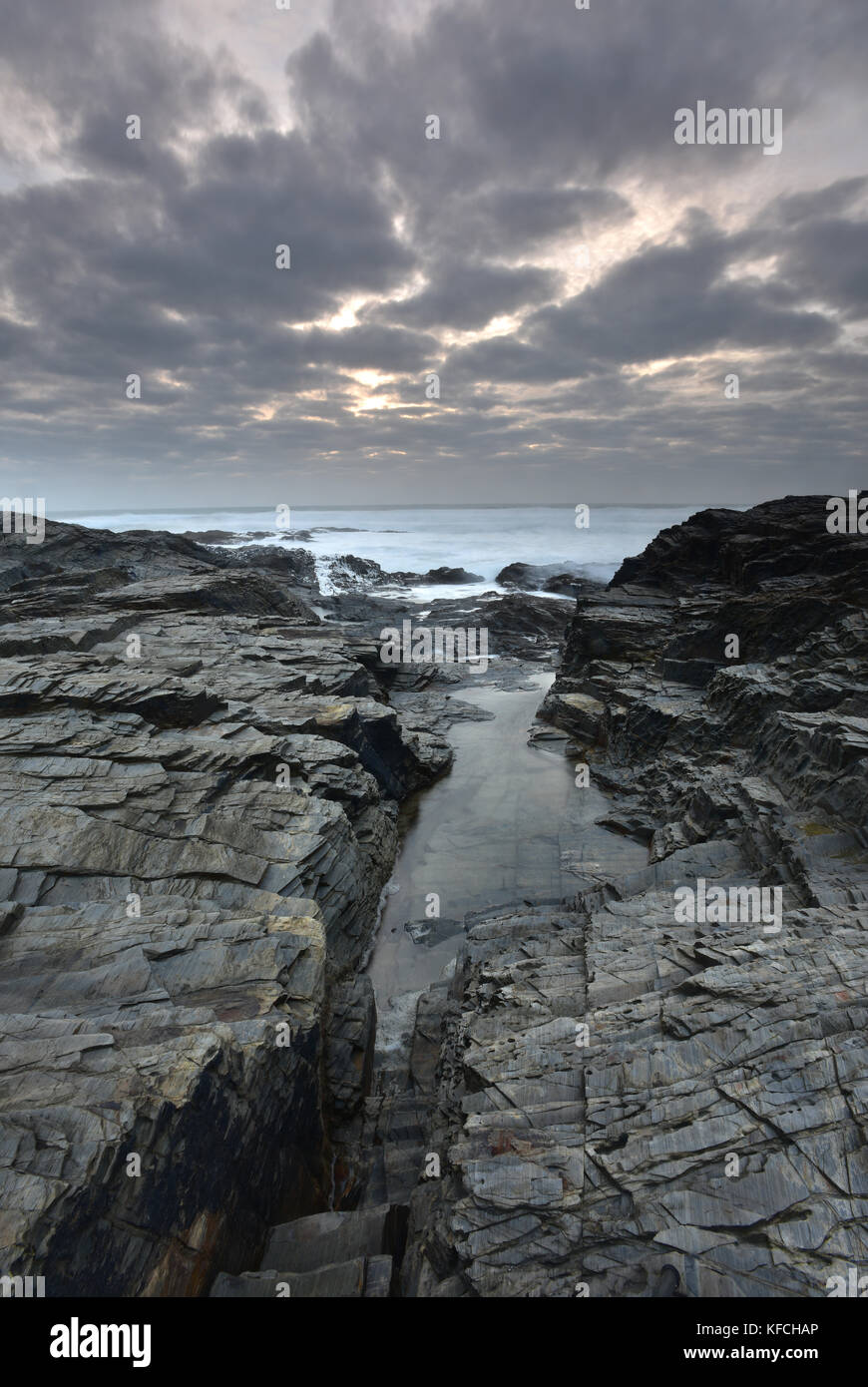 the rocky and rugged atmospheric Cornish coast on a stormy evening at sunset in Cornwall. Coastal scenes, Cornwall, - Stock Image