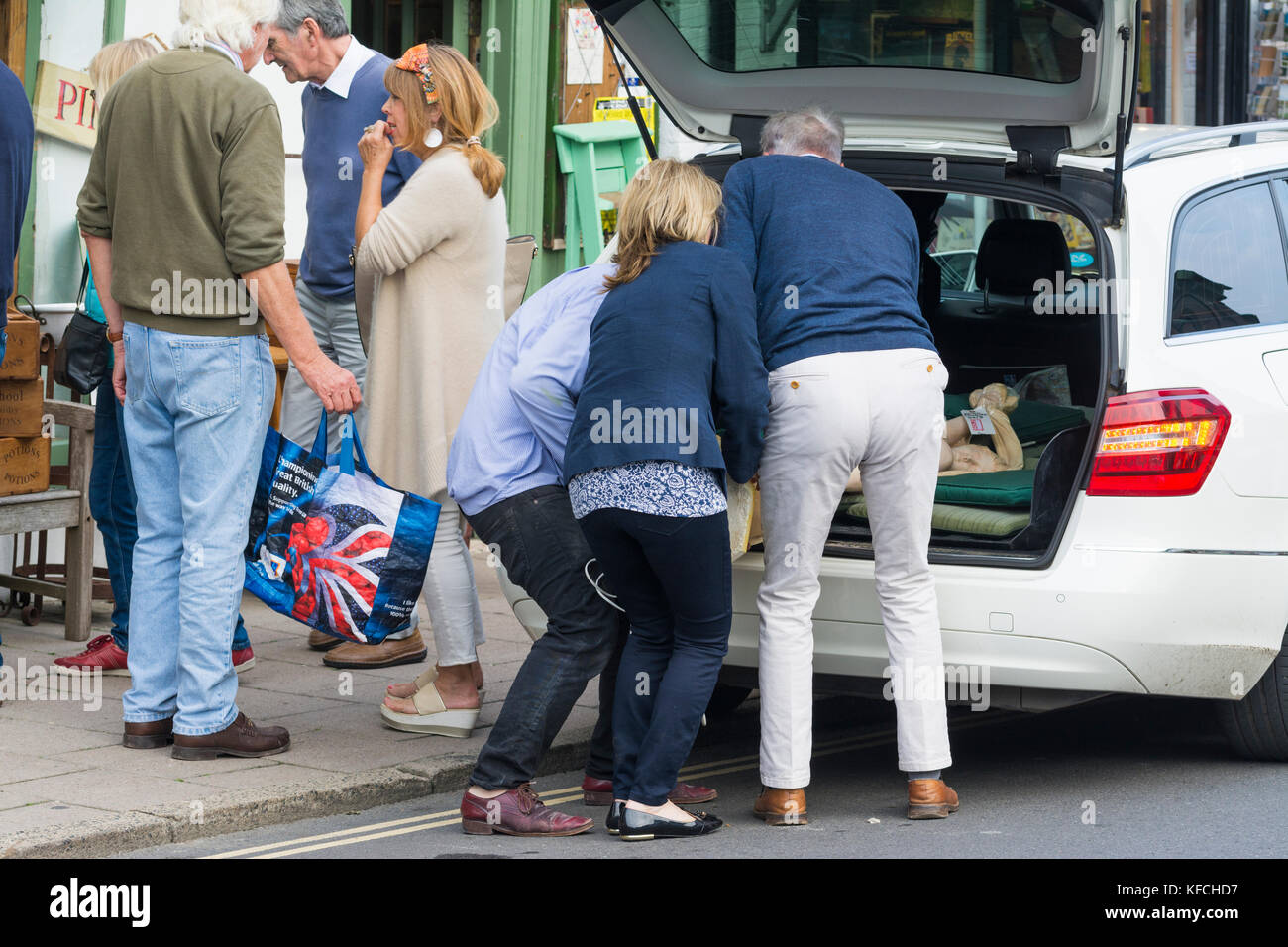 People helping to load up a hatchback car with goods after shopping in the UK. - Stock Image