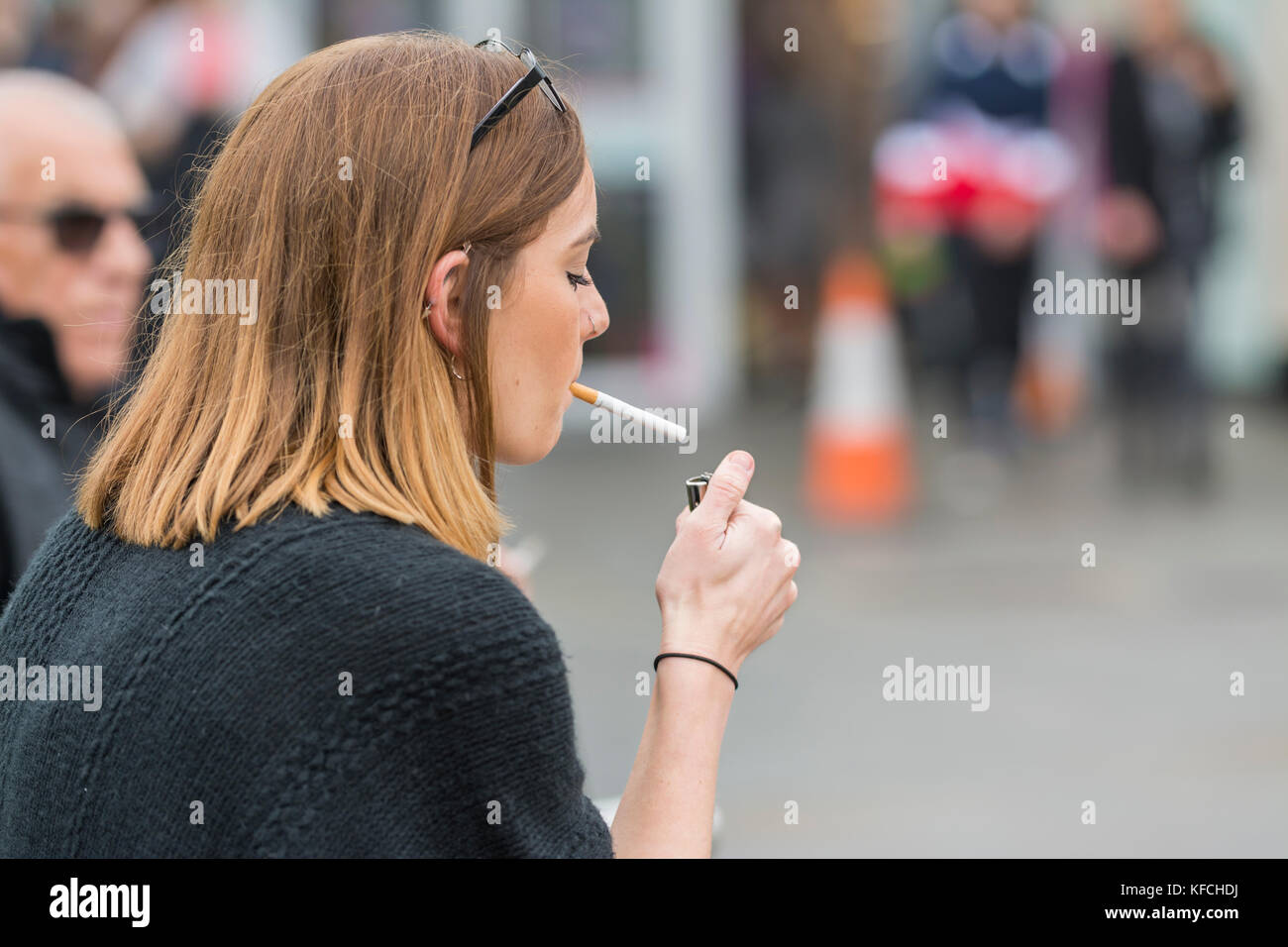 Young woman lighting a cigarette in the UK. Unhealthy lifestyle. - Stock Image