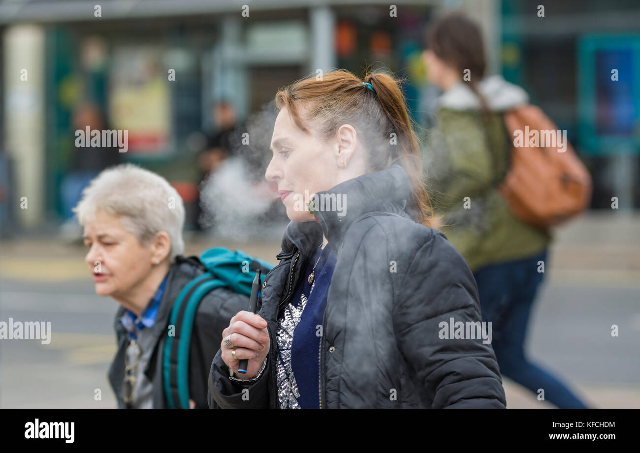 Woman smoking a electronic cigarette. Woman vaping. Female smoking e-cig in the UK. - Stock Image