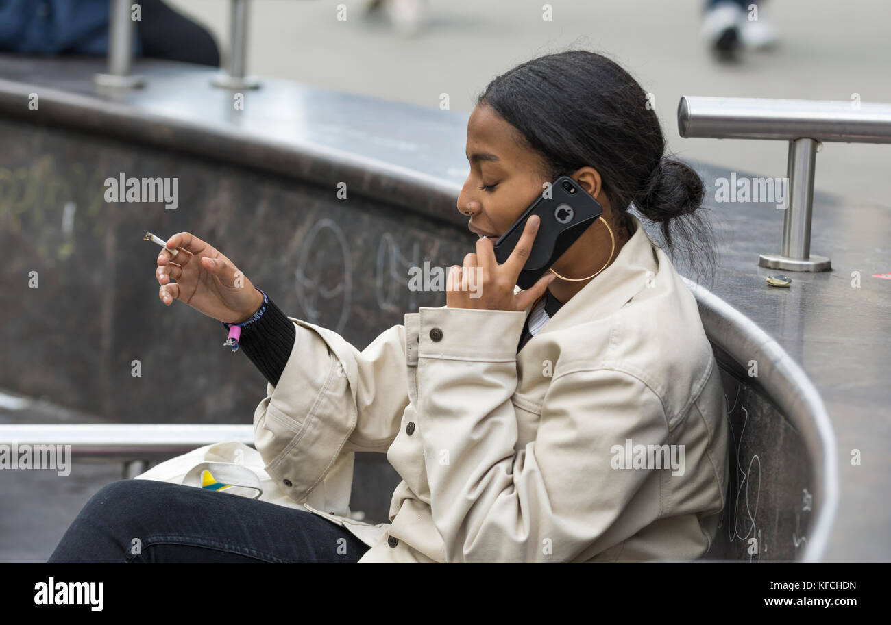 Young black woman using the phone while smoking a cigarette in the UK. - Stock Image