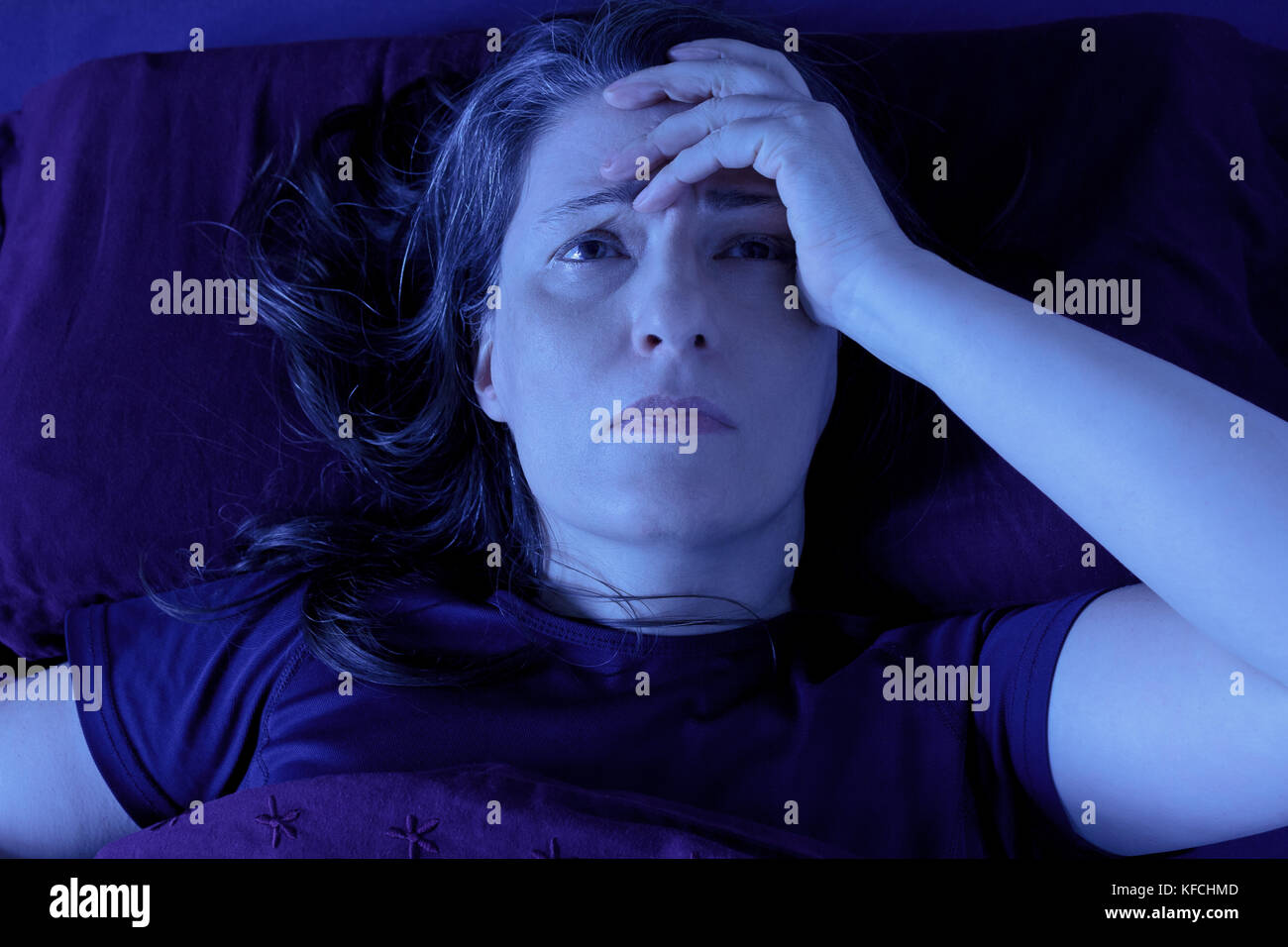 Middle aged woman lying awake in her bed at night because of insomnia, stress, fears, nightmares or illnesses like Stock Photo