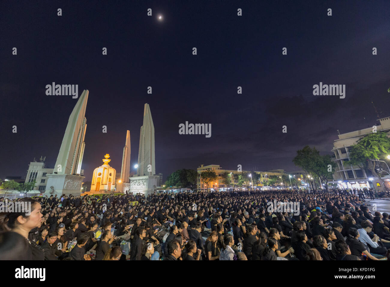 BANGKOK, THAILAND - OCTOBER 26: Unidentified mourners in black sit and watch the royal activities for the cremation of Rama 9, the former king next to Stock Photo