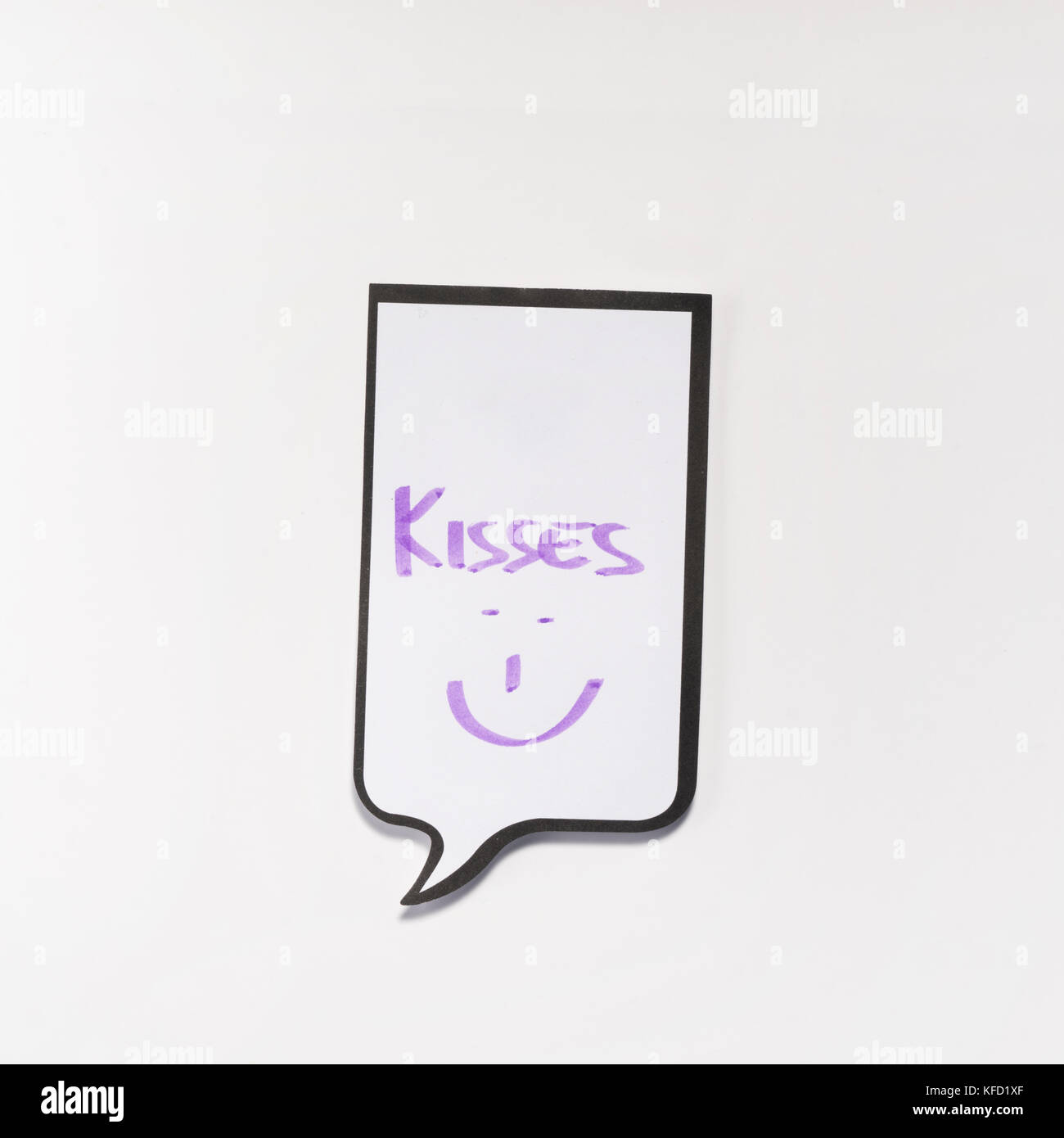 a white memo pad with the shape of a comic with the inscription 'kisses' - Stock Image