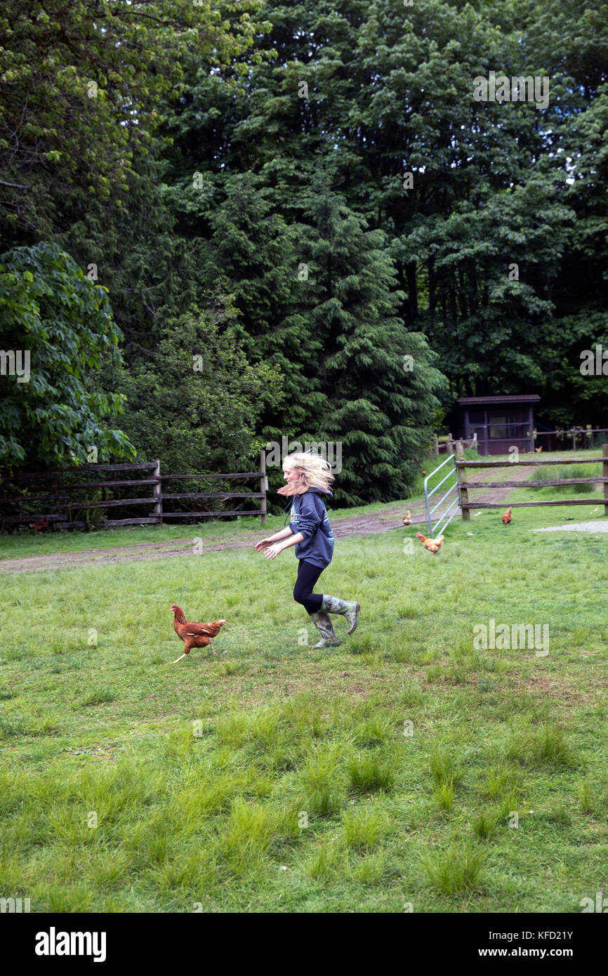 CANADA, Vancouver, British Columbia, young girls chase chickens in Port Graves, Gambier Island, Howe Sound - Stock Image