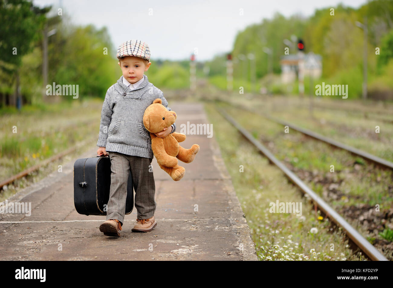 Little boy goes with a suitcase and a teddy bear at the train station - Stock Image