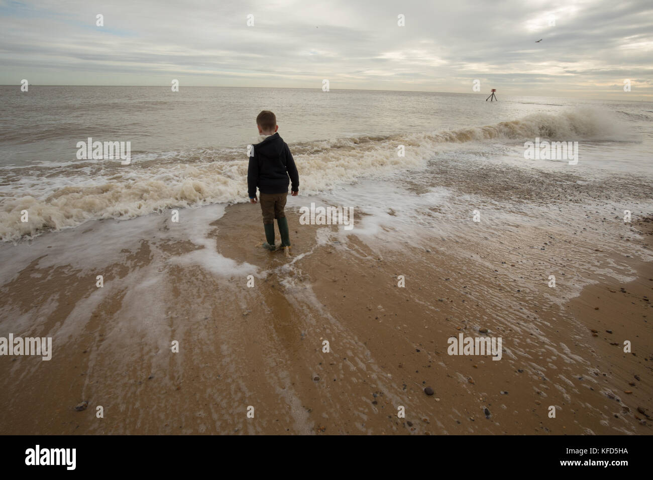 Boy contemplating the waves on an Autumn beach in Suffolk, England. - Stock Image