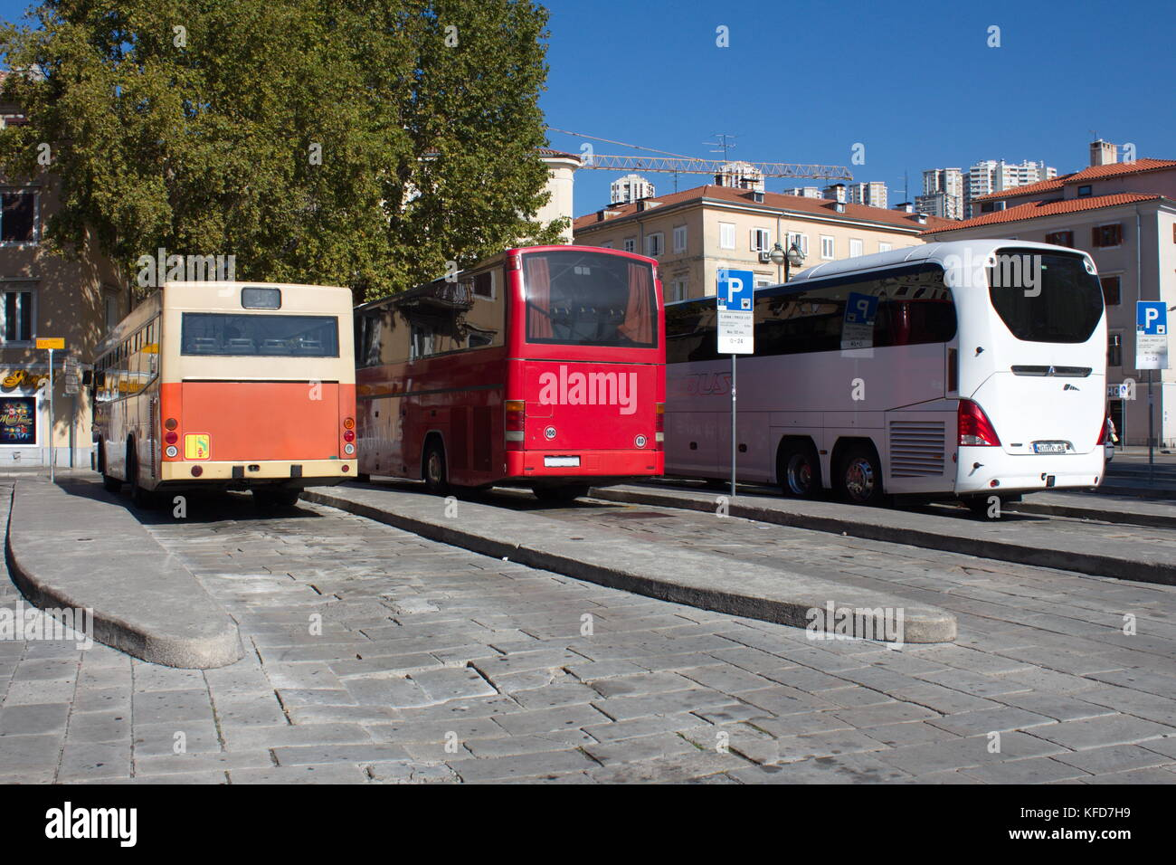 Three generation of buses parked at local bus station, raging from oldest and smallest to newest and largest - Stock Image