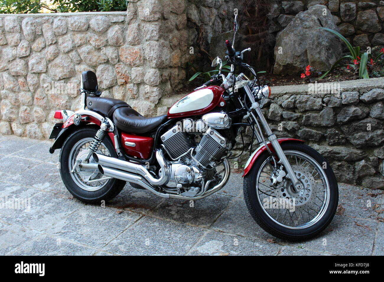 Modern new and polished red and chrome chopper parked in front of stone wall with flowers planted in the middle - Stock Image