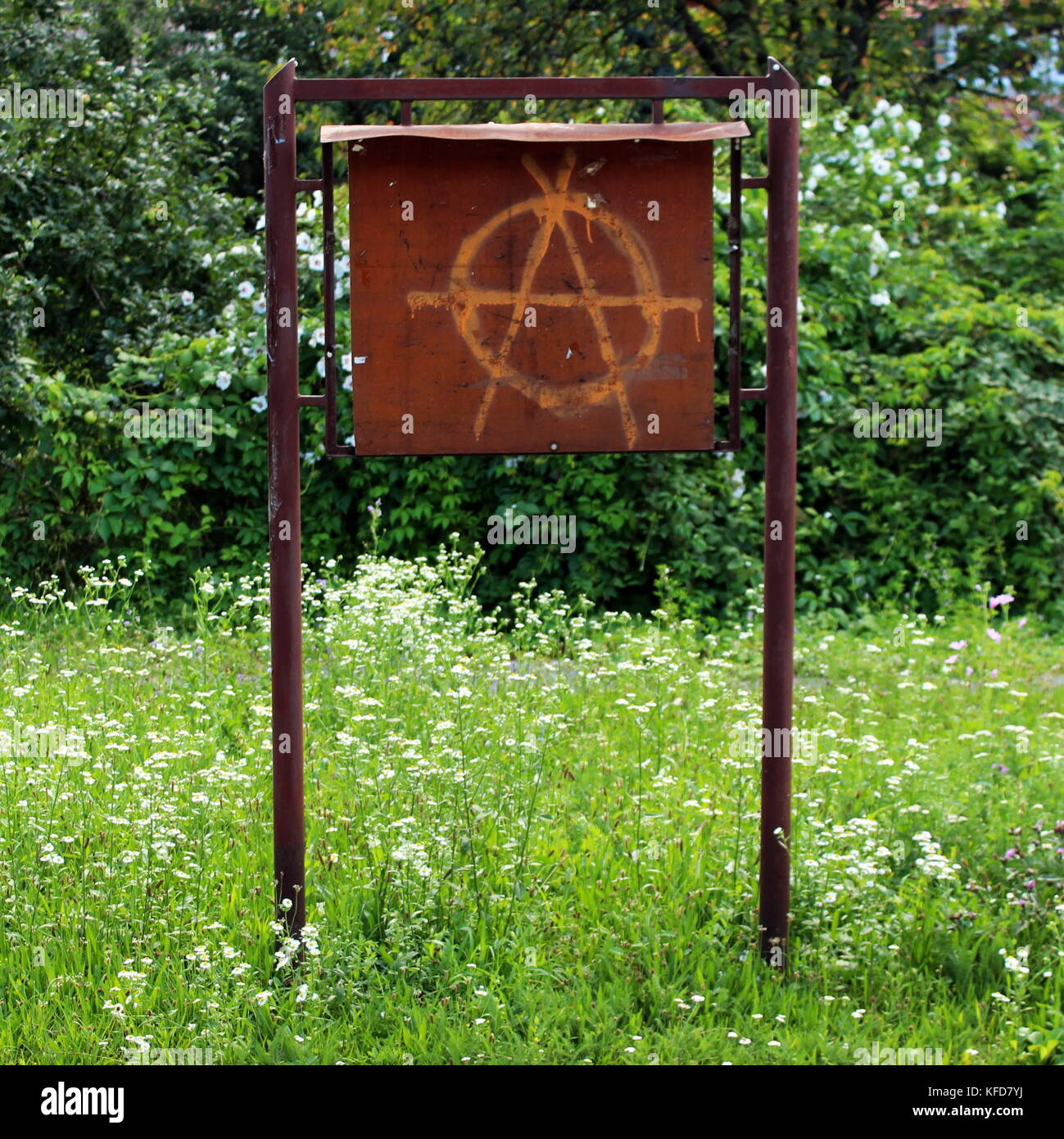 Anarchy graffiti painted on an old brown metal notice board (metal place for local for announcements) surrounded - Stock Image