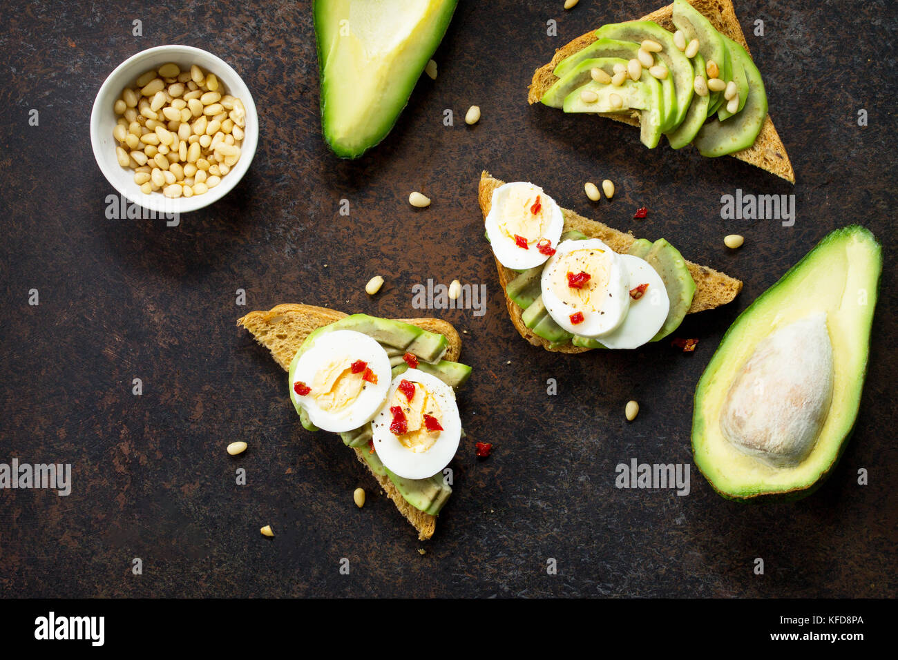 Sandwich avocado with fresh sliced avocado, egg poached and spices on a dark slate or stone background. Copy space. Stock Photo