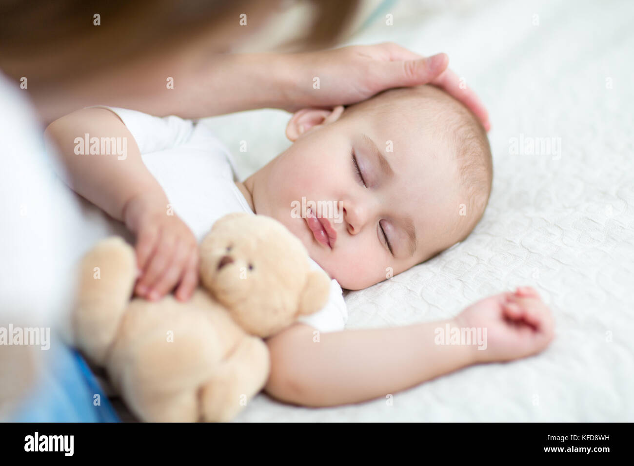 Motherhood. Parenthood. Young mother looking at her baby infant sleeping in bed - Stock Image
