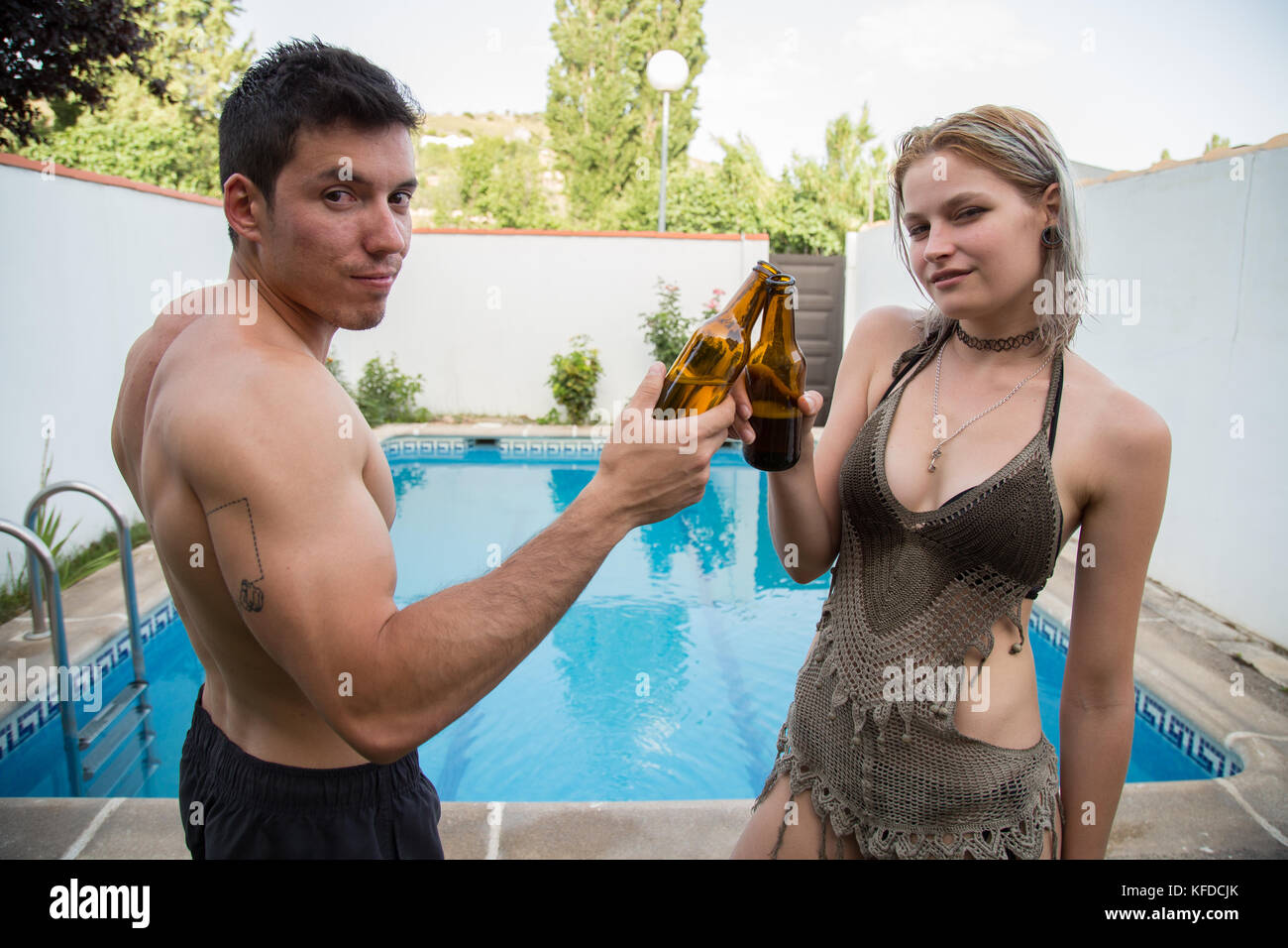 79ea825a47 Spanish boy and young Russian woman in swimsuits posing in pool and  clinking beer bottles.