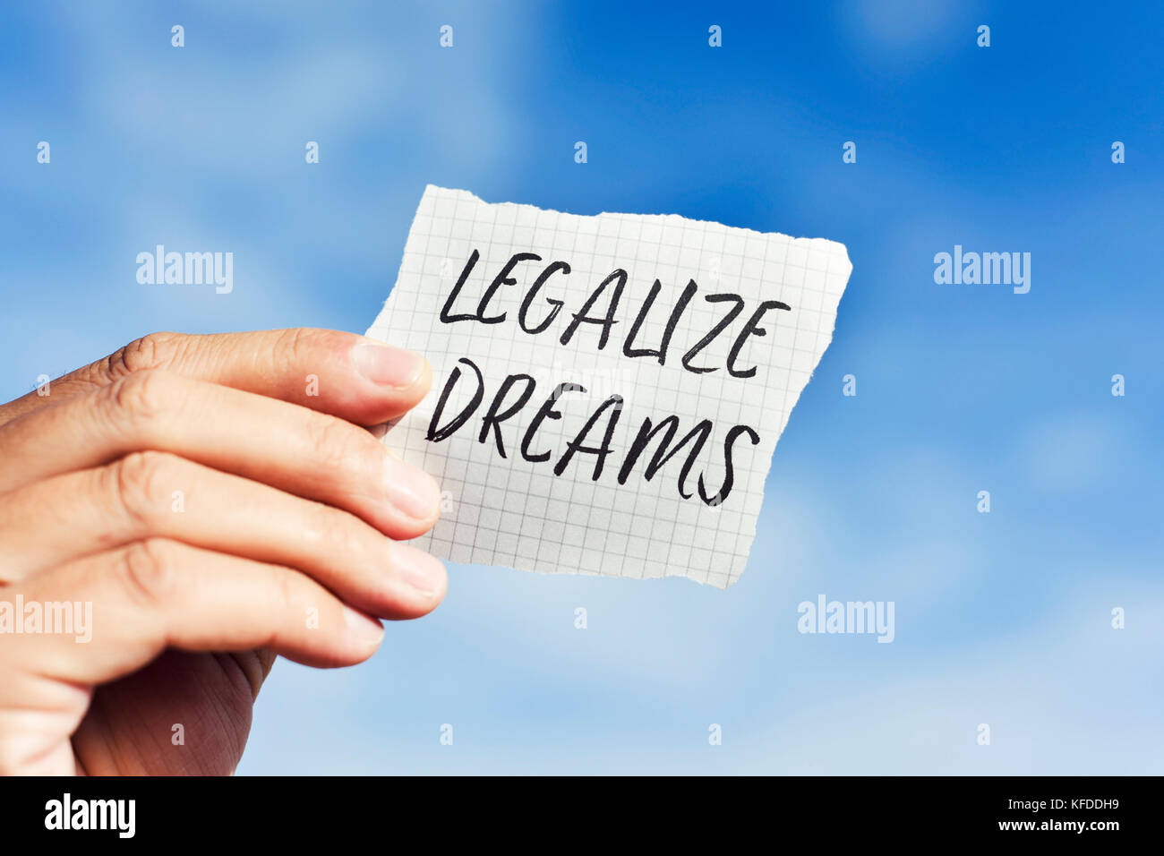 closeup of the hand of a young caucasian man holding a pieces of paper with the text legalize dreams written in - Stock Image