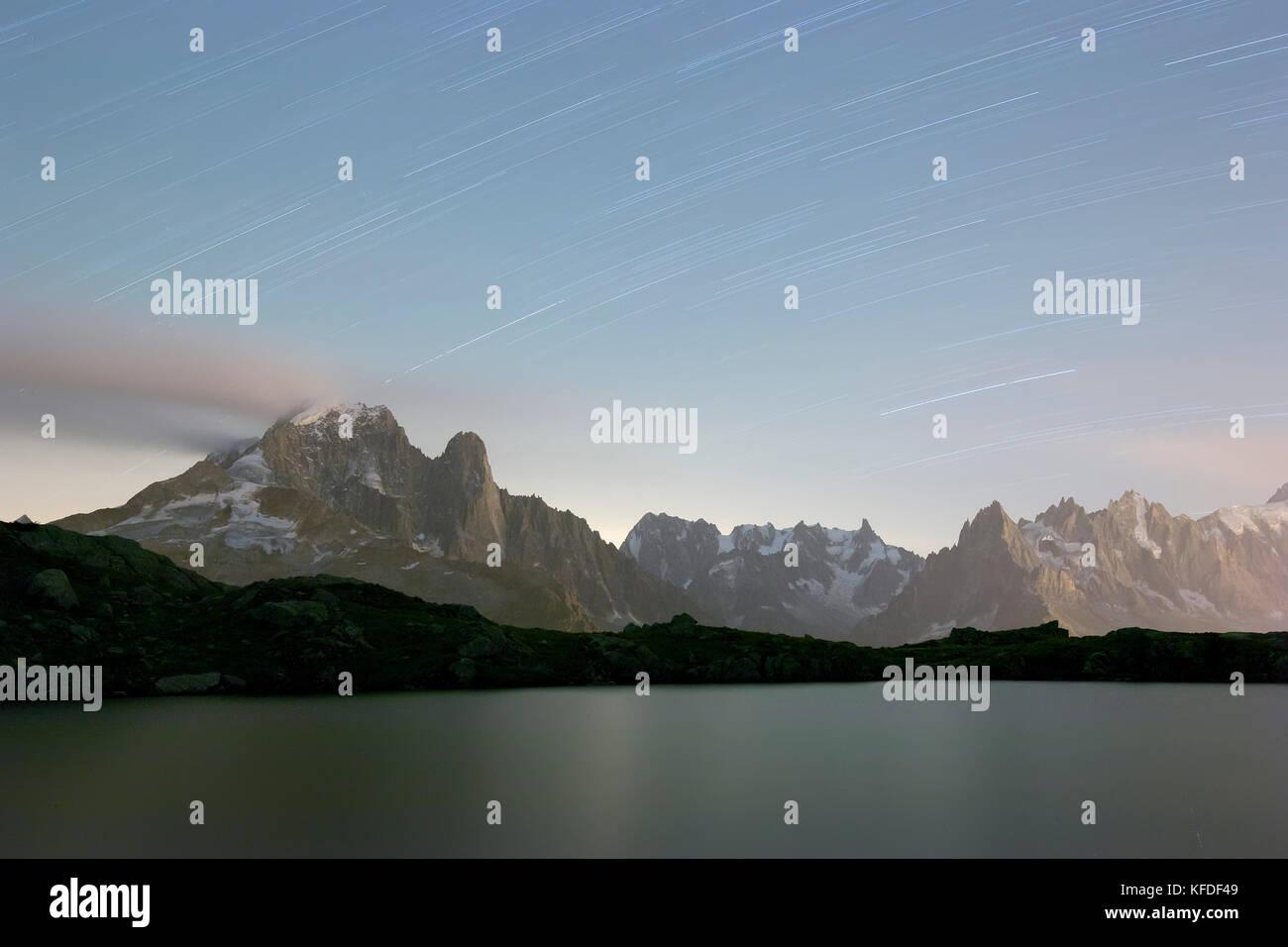 Star trail on the rocky peaks of Les drus and Aiguille Verte, Lacs De Cheserys, Chamonix, Haute Savoie, France Stock Photo