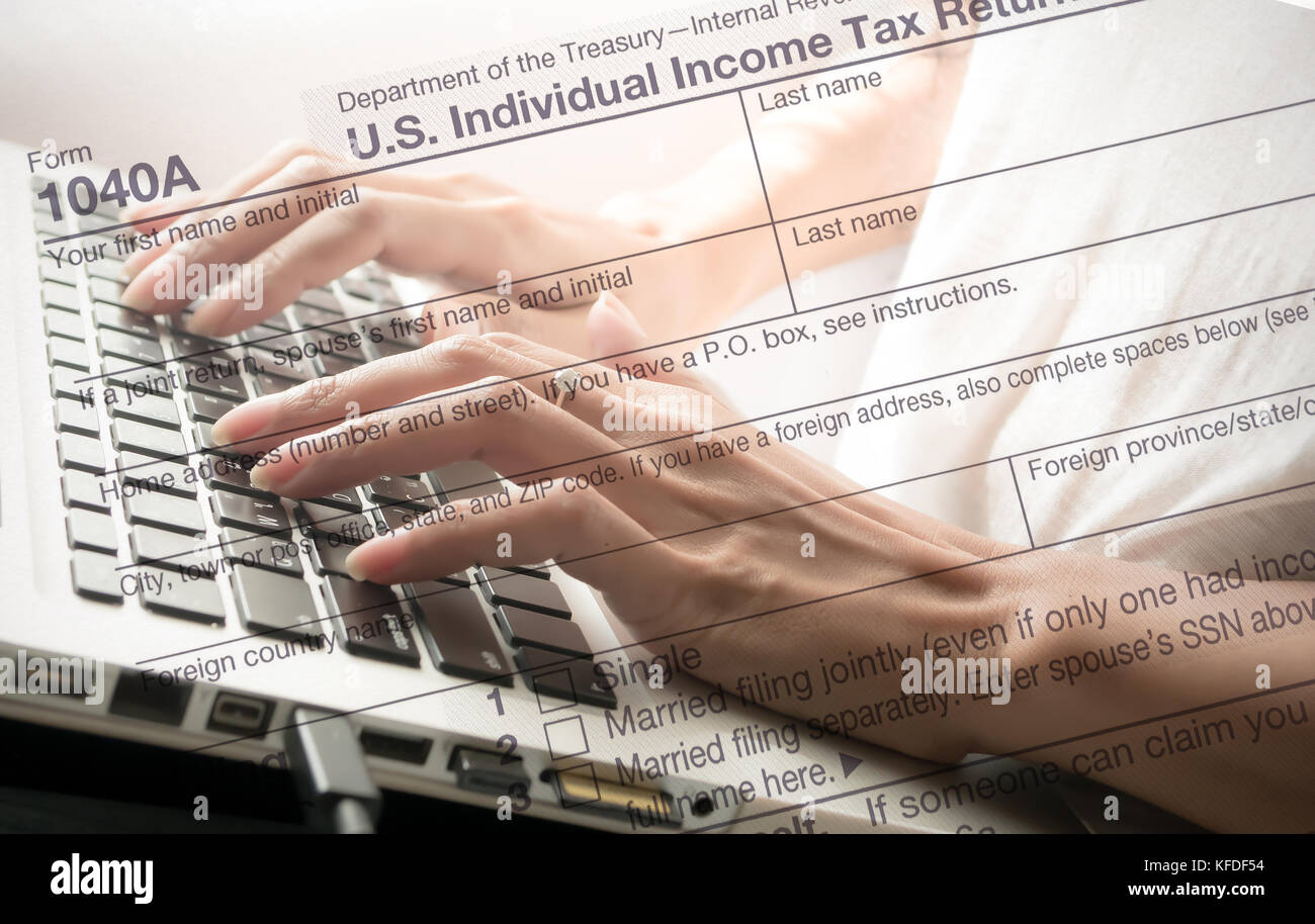 Double Exposure hand typing laptop with US tax form/ taxation concept - Stock Image