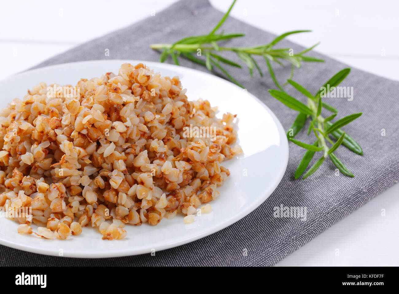 plate of cooked buckwheat on grey place mat - close up - Stock Image