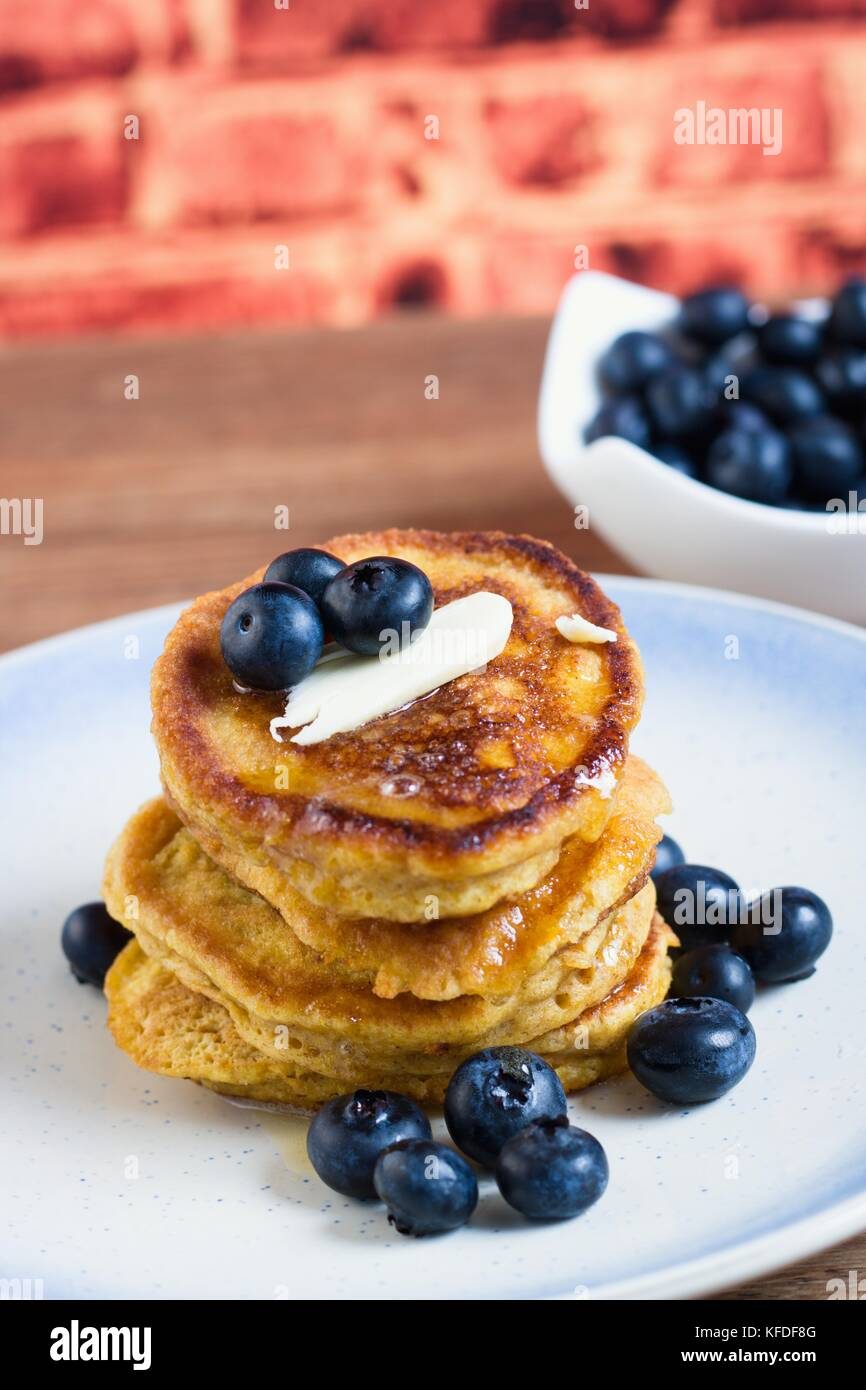 Stack of fresh homemade gluten free pancakes with blueberries, butter and syrup in front of brick wall background - Stock Image
