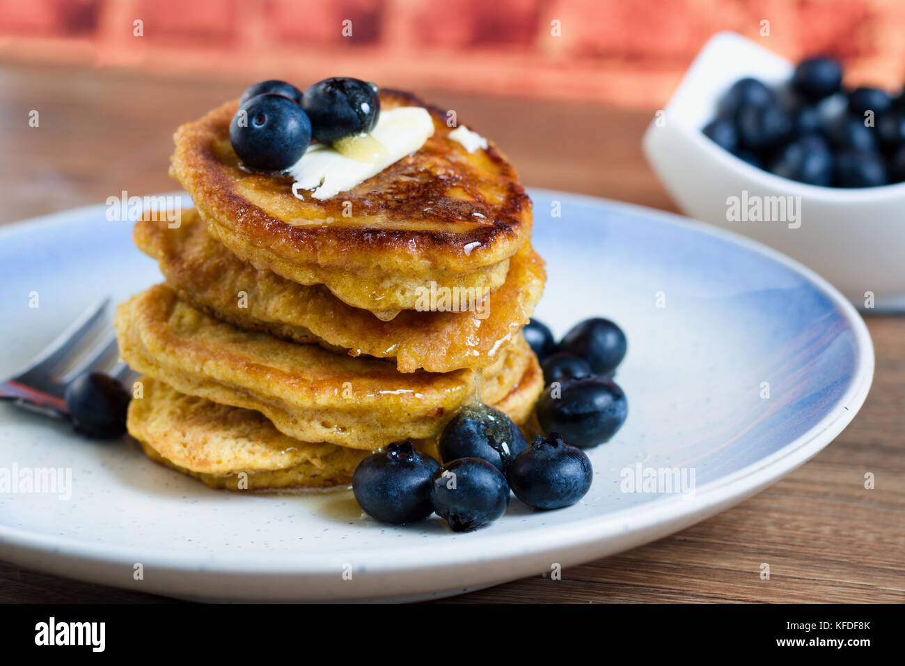 Stack of fresh hot pancakes with blueberries, butter and syrup in front of brick wall background - Stock Image