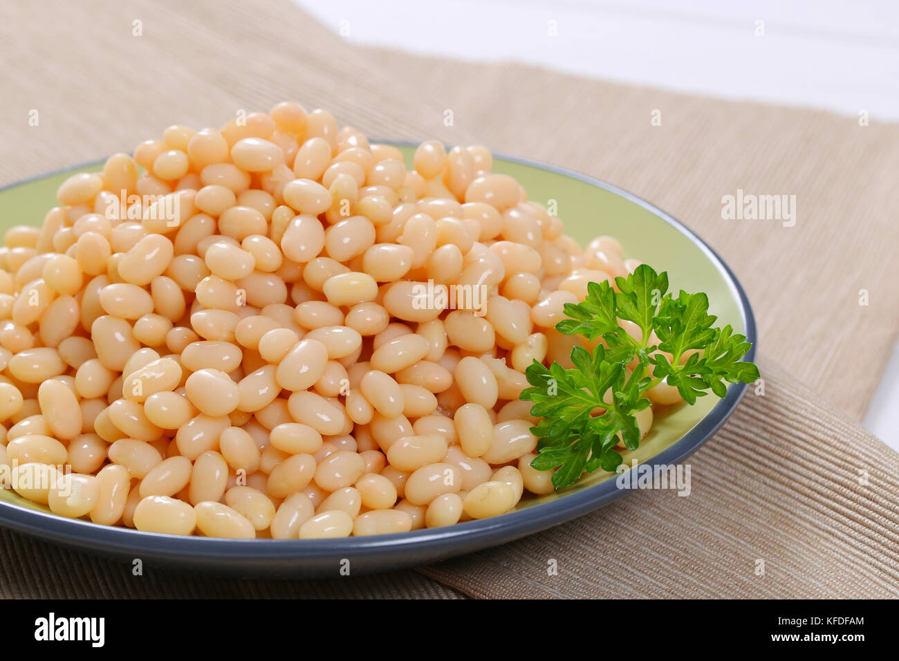 plate of canned white beans on beige place mat - close up - Stock Image