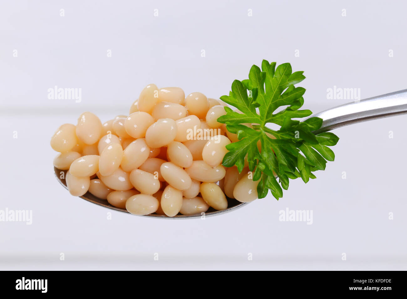 spoon of canned white beans on white wooden background - Stock Image