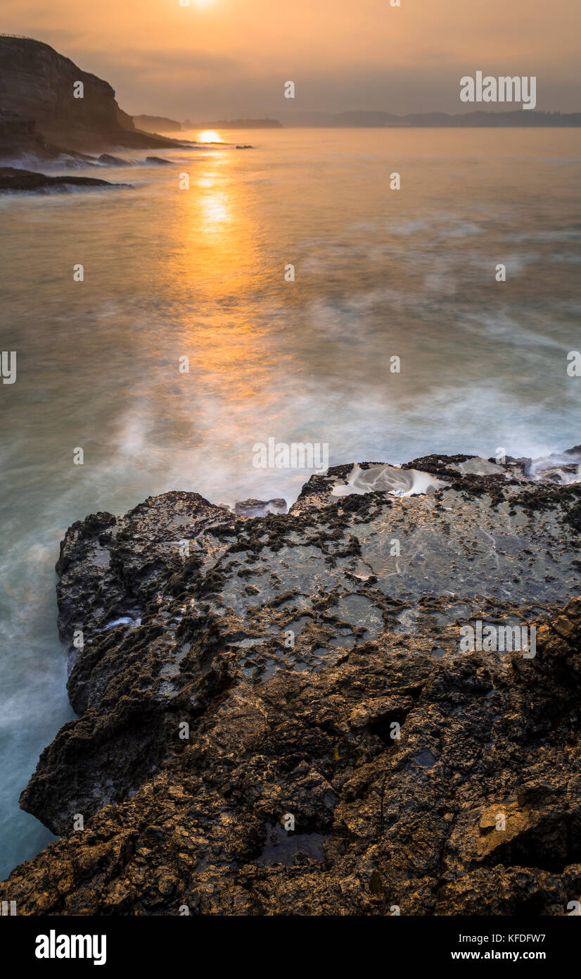 Natural salt water pool formed over the sea at sunset - Stock Image