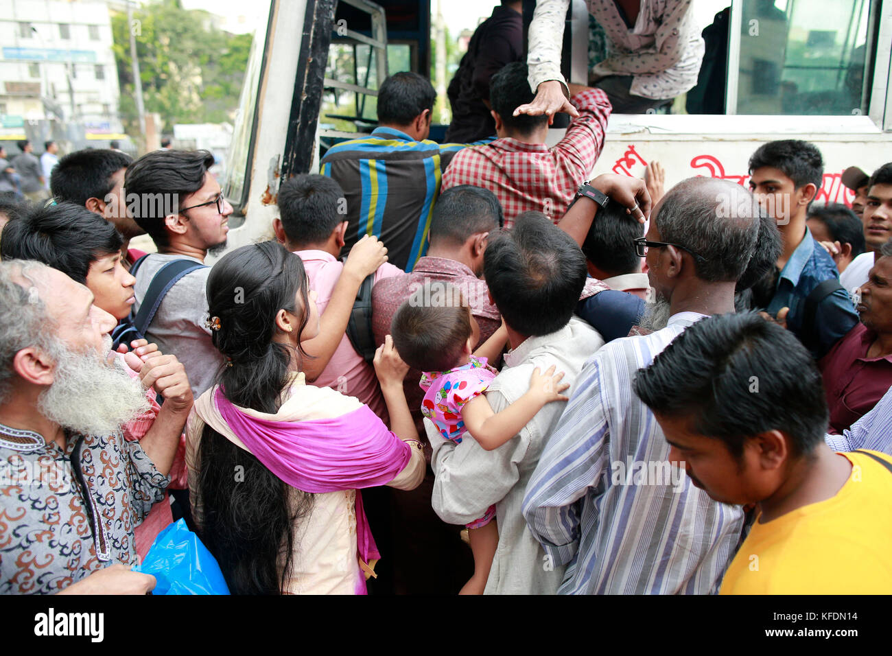 Bangladeshi people try to ride in of an overcrowded bus to travel home, as others wait for transport ahead of Iftar, Stock Photo