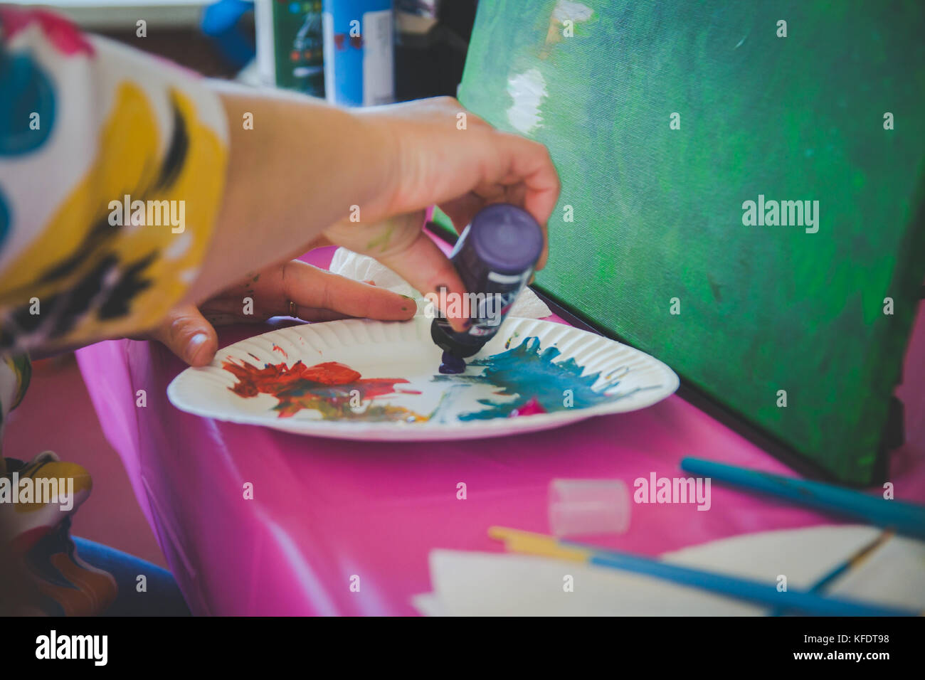 Artist holding paint brush painting canvas - Stock Image