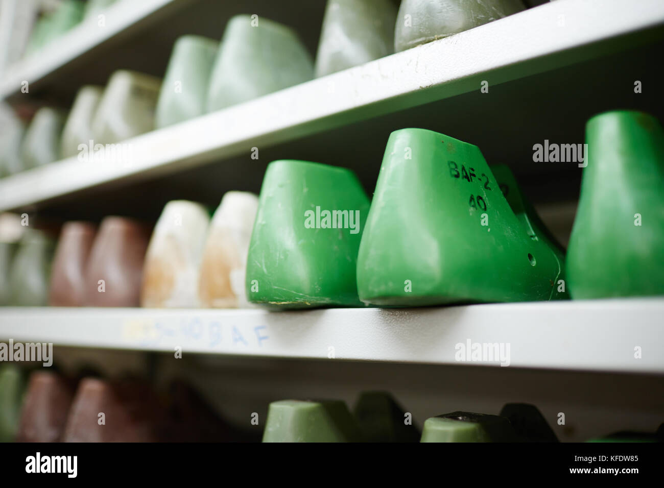 Rows of model forms of footwear on shelves of shoemaker workshop - Stock Image