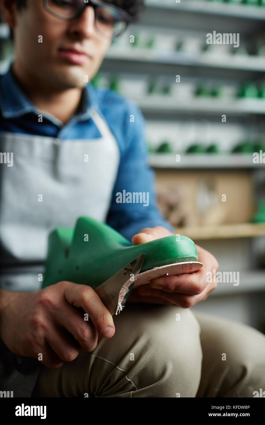 Footwear form in hands of cobbler while he cutting out its sole - Stock Image