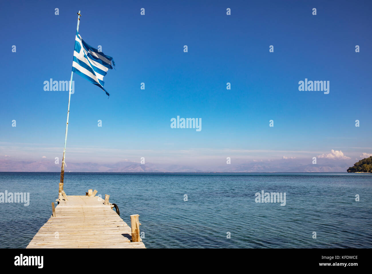 Wooden jetty or a pier on the Ionian Sea - a part of Mediterranean Sea, dark blue sky, autumn in Greece, Ionian - Stock Image