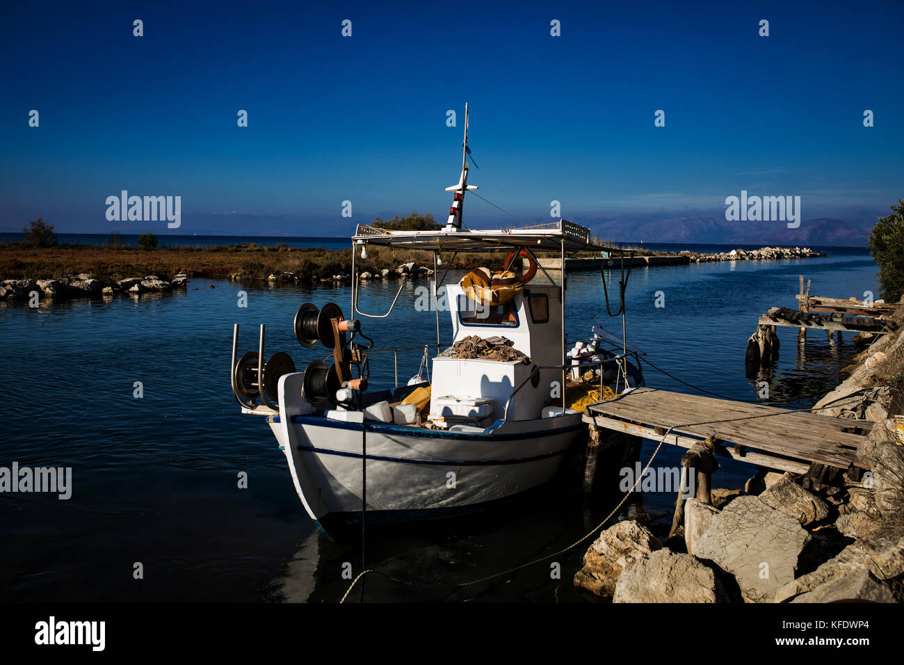 A fishing boat in a canal, river, close to the town Lefkimmi, Ionian Islands, Greece. Blue sky, sun, holidays in - Stock Image