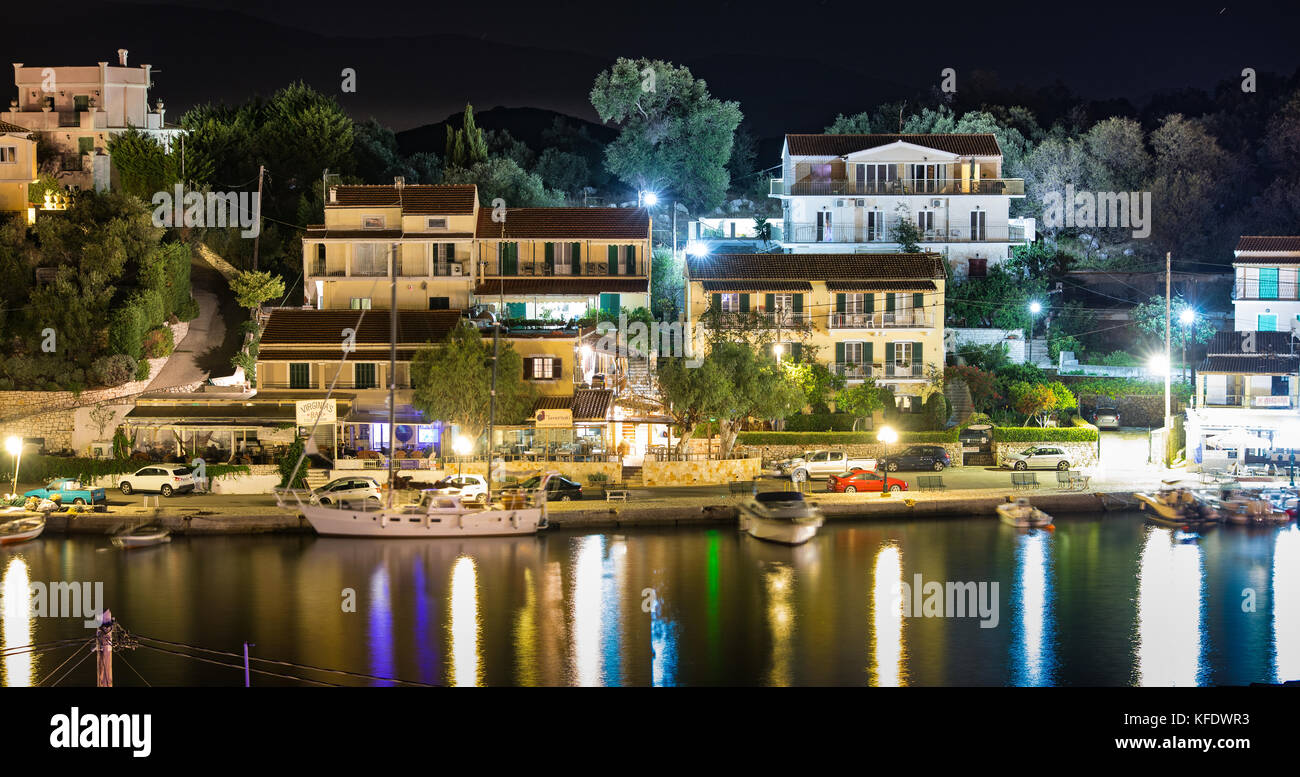 The bay, marina and harbor of Kassiopi as seen from above in the night. Colorful water reflections. Corfu, Greece. - Stock Image