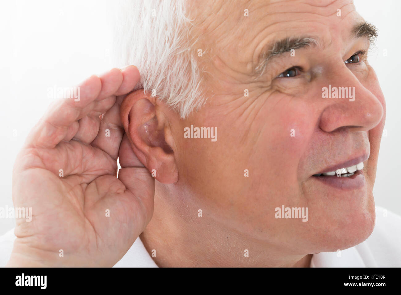 Senior Man Trying To Hear With Hand Over Ear - Stock Image