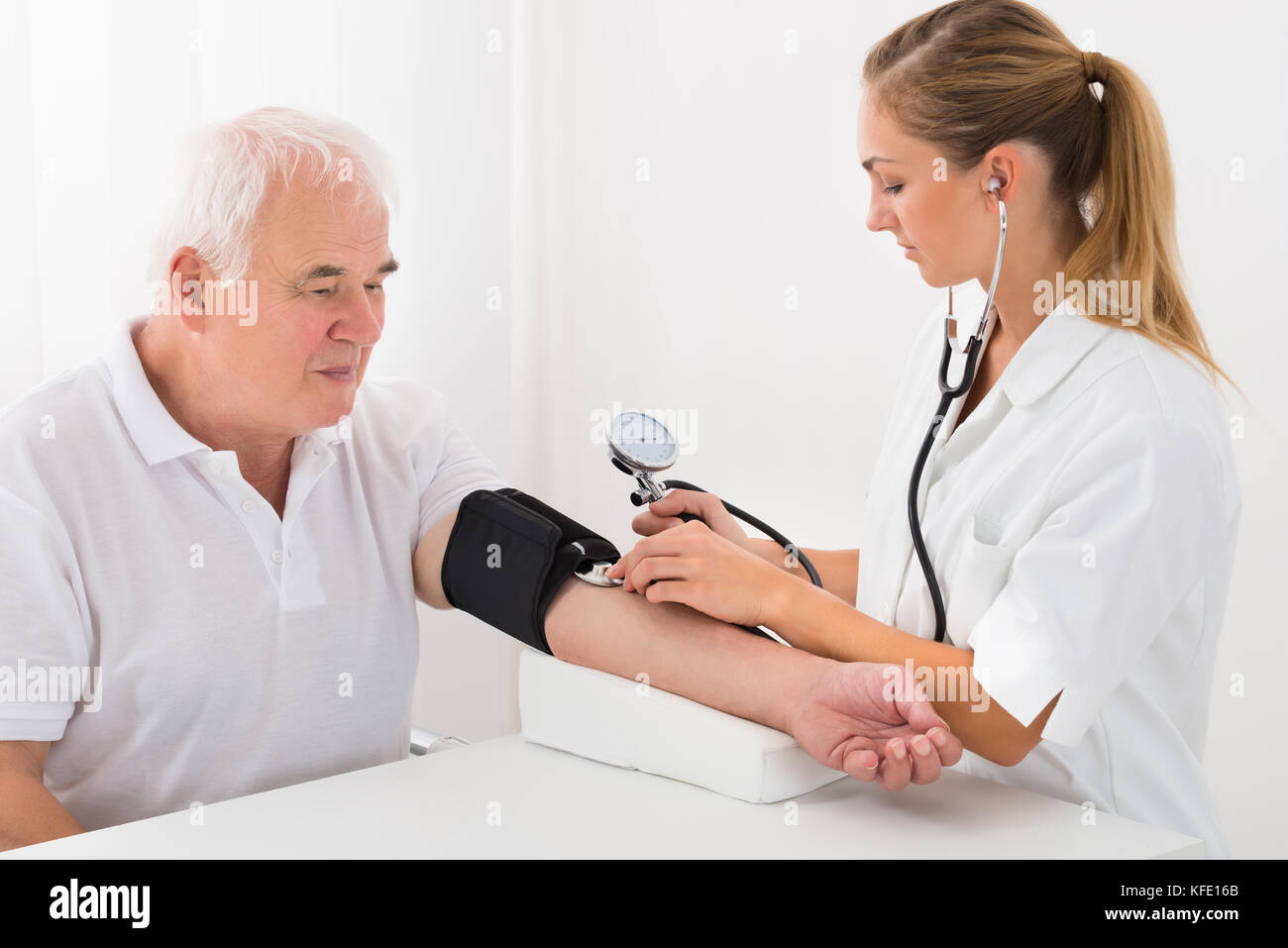 Young Female Doctor Checking Blood Pressure Of Senior Male Patient In Clinic - Stock Image