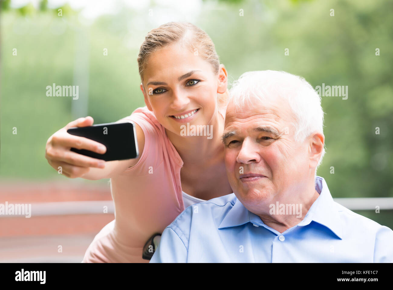 Close-up Of A Smiling Young Woman With Her Father Taking Selfie On Mobile Phone - Stock Image