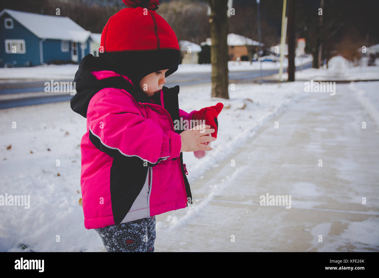 infant putting a mitten on during winter - Stock Image