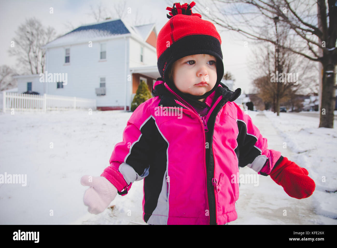 Infant standing in snow wearing winter clothes - Stock Image