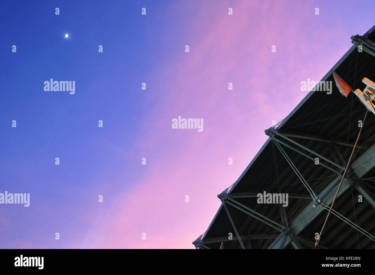 moon on twilight sky over football stadium roof - Stock Image