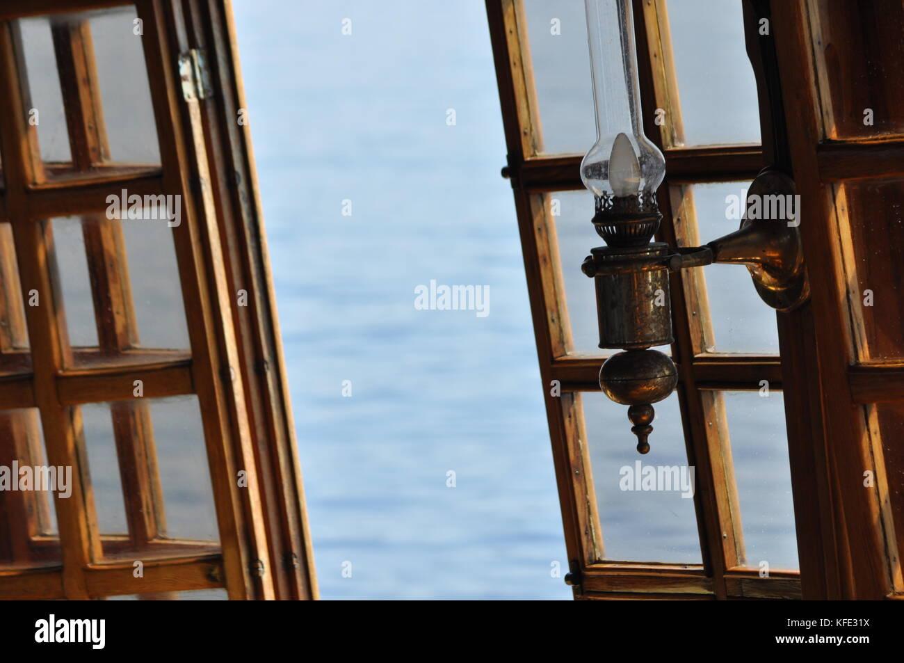 Sea view through the open window. Kerosene lamp on the ship. - Stock Image