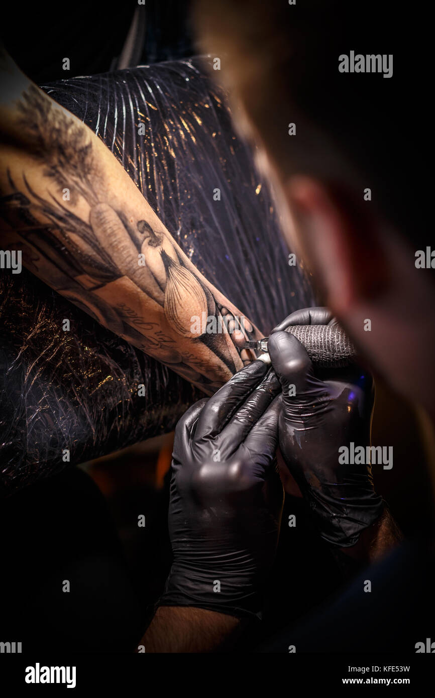 Close up tattoo artist demonstrates the process of getting black tattoo - Stock Image