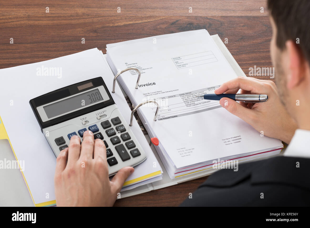 Photo Of Businessman Analyzing Invoice With Calculator - Stock Image