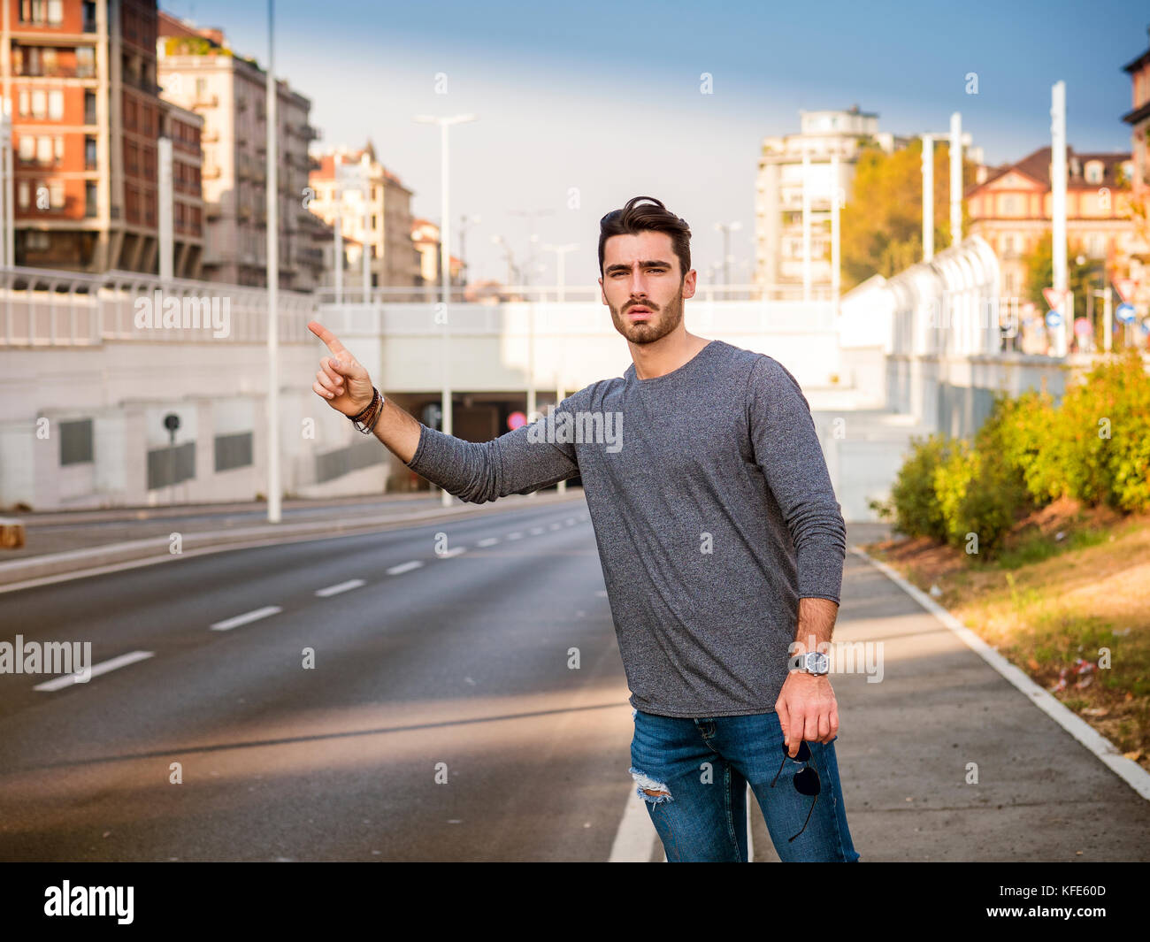 Young man stopping a taxi cab - Stock Image