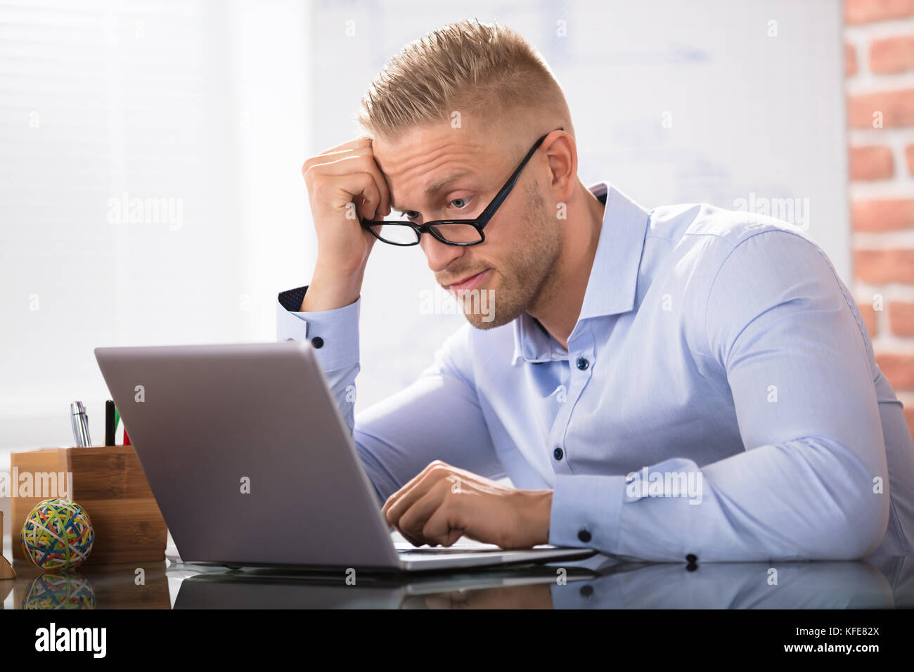 Contemplated Businessman Sitting With Laptop At Workplace - Stock Image